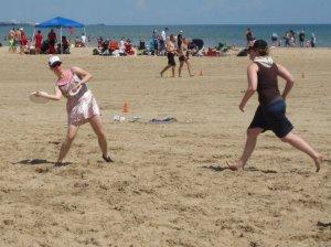 Photo of Stephanie Folk playing Ultimate Frisbee on the Lake Michigan beach.