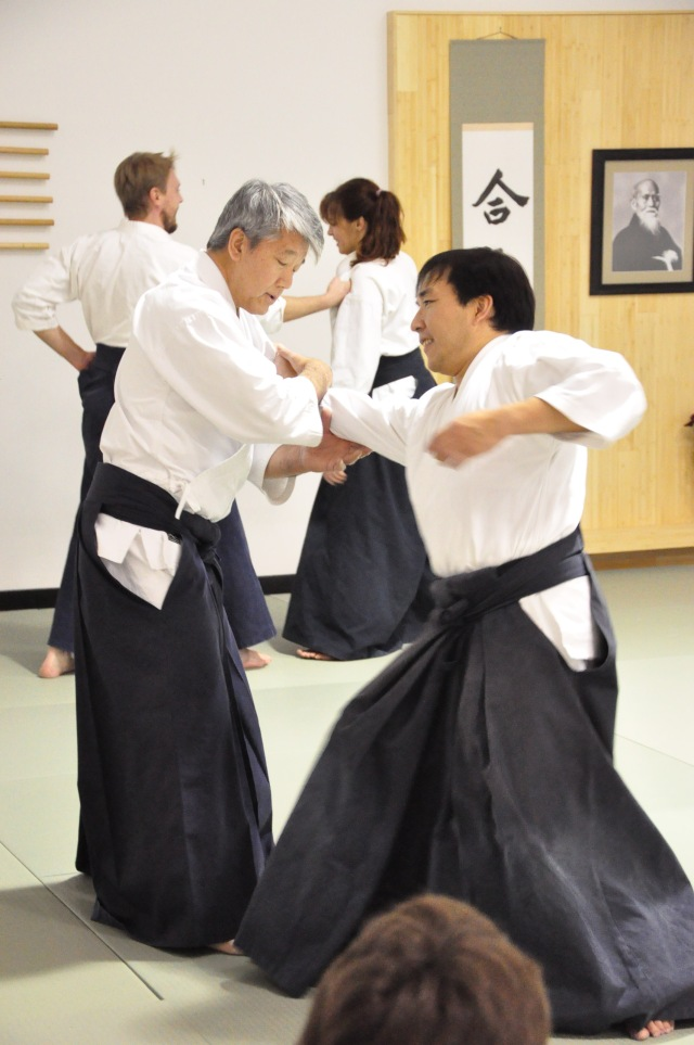 image of Ikdea Sensei trains with Dwight Sora as Elizabeth Margetich and John Gralton work out in the background.